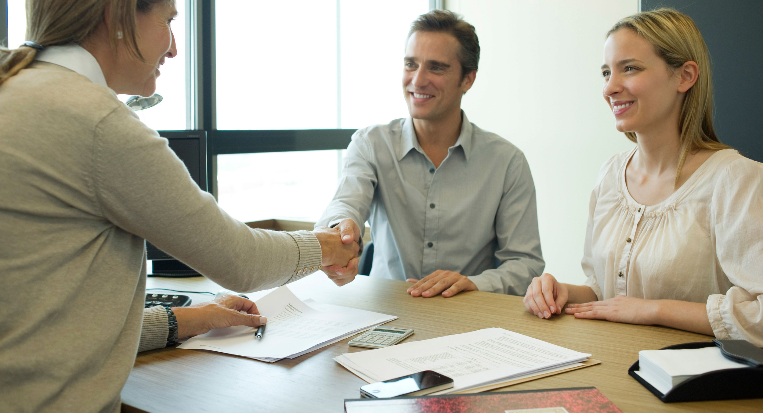 ccbm9f-couple-shaking-hands-with-businesswoman-in-office-cli-2